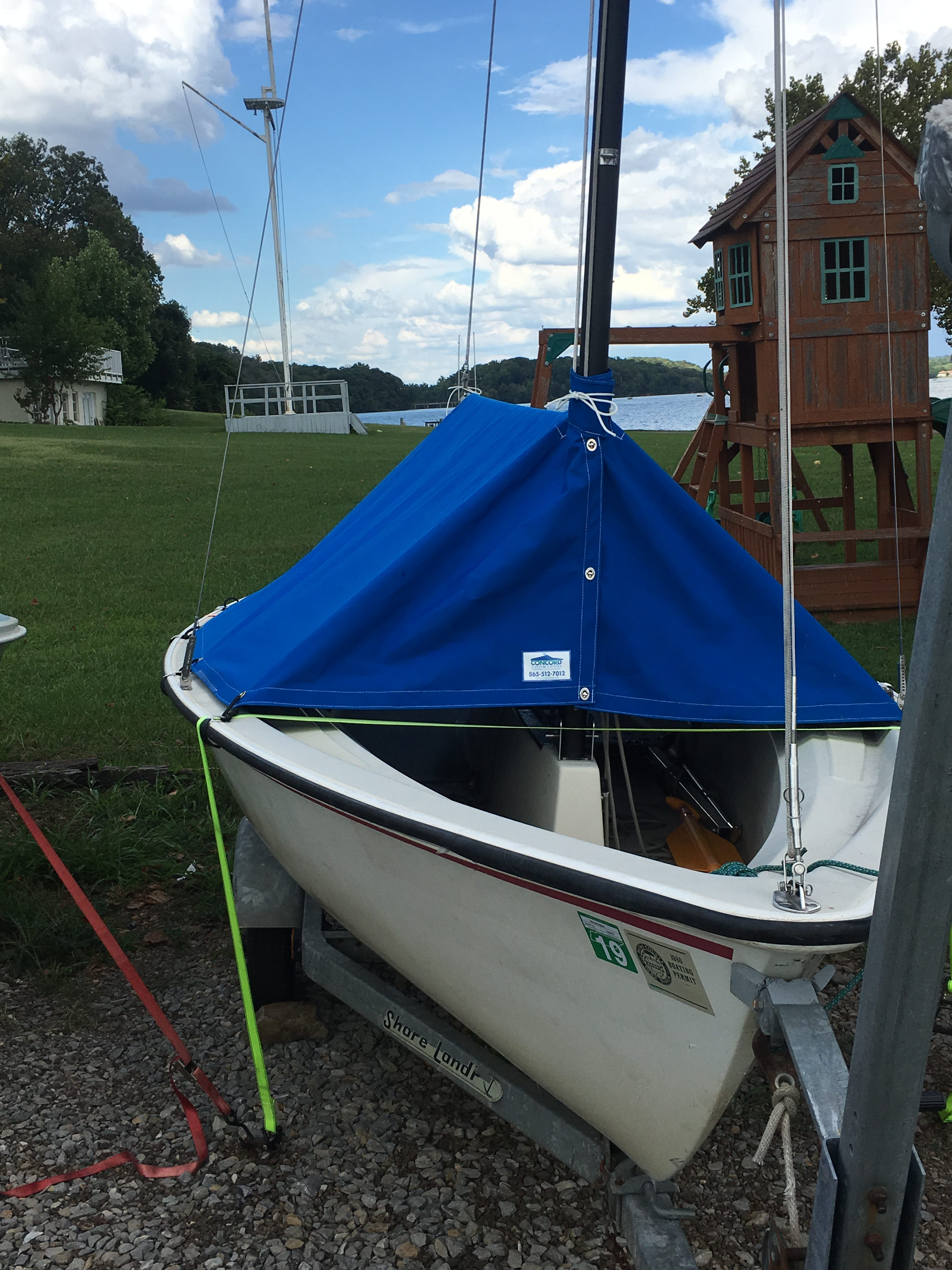 Sailboat with custom boom cover and metal bracket attachments.